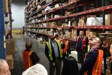 Workers in a Bunzl Safety warehouse looking at the shelves.