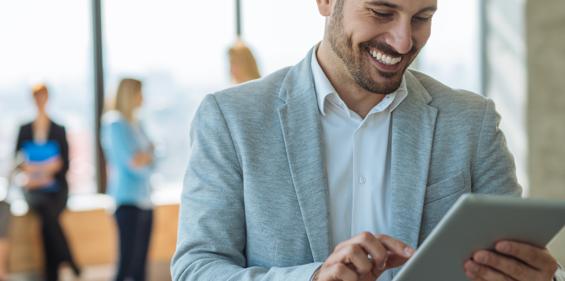 Jeune homme souriant en tenue de travail qui regarde une tablette avec ses collègues en arrière-plan.