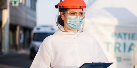 Une experte de Bunzl-Sécurité portant un EPI jetable blanc, un casque de protection, un écran facial et un masque, qui mène une évaluation du site.