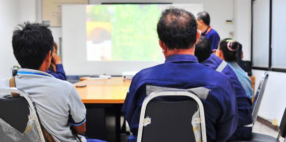 Vue de Bunzl-Sécurité tenant une séance de formation pour un client avec des employés assis autour d'une table de conférence.