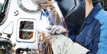 Close crop image of an automotive technician wearing Bunzl Safety protective gear and working on a part.