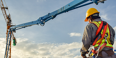Image of a man wearing a yellow hard hat and a full body harness facing a crane.