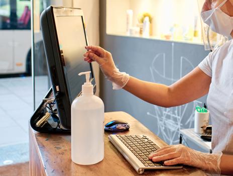 Une récolte rapprochée d'un travailleur de la santé devant un ordinateur avec une bouteille de désinfectant pour les mains Bunzl Safety à côté de son écran d'ordinateur.