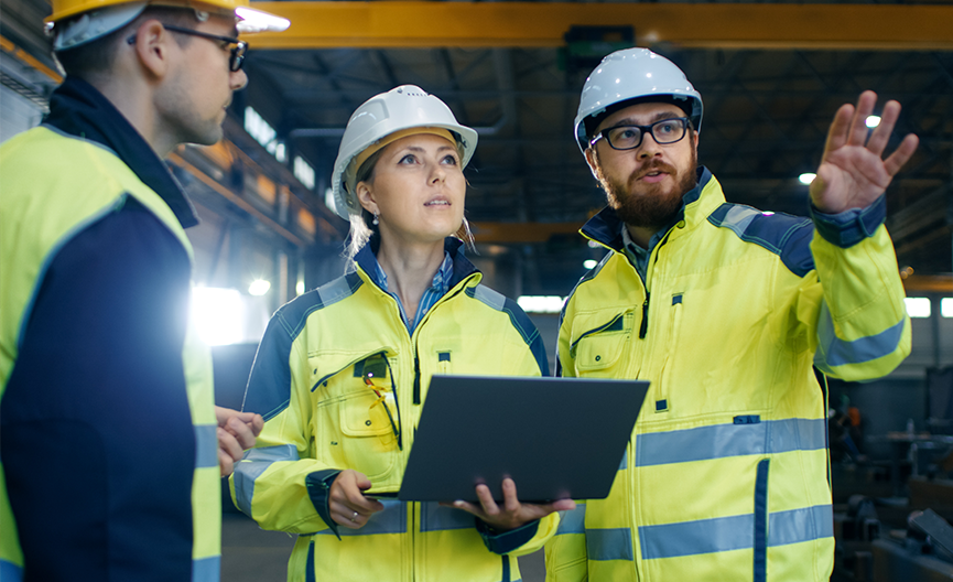 Two male and one female worker in an industrial plant wearing safety vests and hard hats from Bunzl Safety.