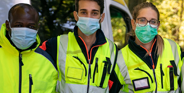 A group of city workers wearing Bunzl Safety flourescent safety vests and masks standing in front of a truck facing the camera.