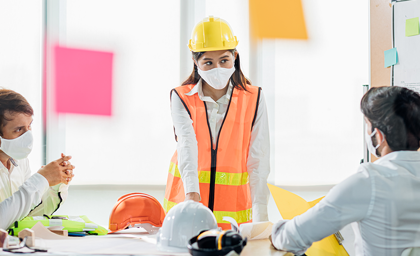 Female employee wearing flourescent safety vest and yellow hard hat with a mask on standing at the head of a table speaking to other employees who also have their protective gear on the table.