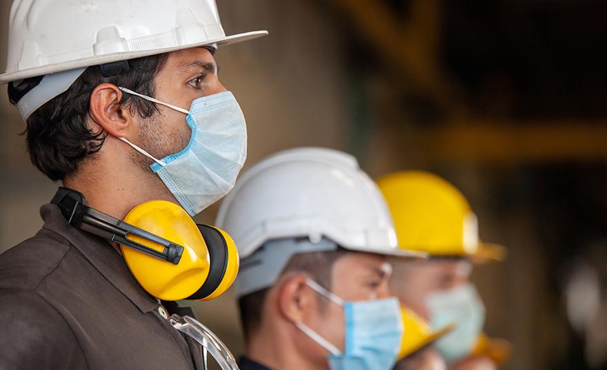 Photo de profil d'un groupe d'employés alignés qui portent des casques de protection, des protecteurs d'oreilles et des masques Workhorse de Bunzl-Sécurité