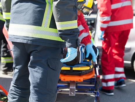 Gros plan d'un groupe d'ambulanciers paramédicaux portant l'équipement de protection de Bunzl-Sécurité, en train de charger une civière.