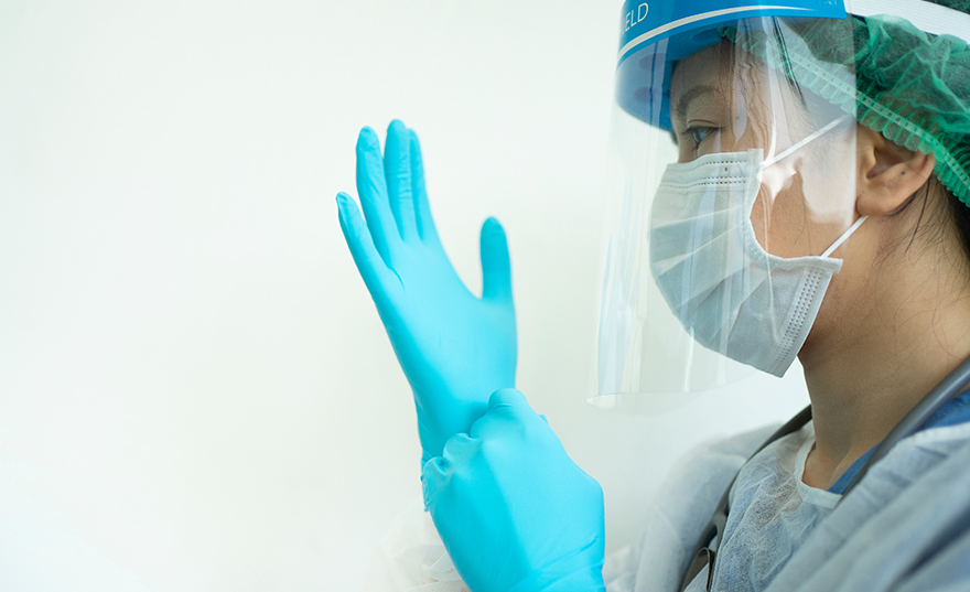 A healthcare professional pulling on vinyl gloves while wearing a surgical mask, hair net and safety shield from Bunzl Safety.