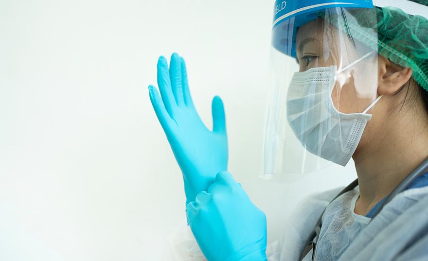 Professionnel de la santé enfilant des gants en vinyle et portant un masque chirurgical, un filet à cheveux et un écran facial de Bunzl-Sécurité.