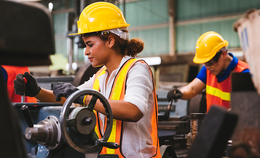 A young female machine operator wearing a yellow hard hat and safety vest with another safety-gear wearing colleage in the background working.