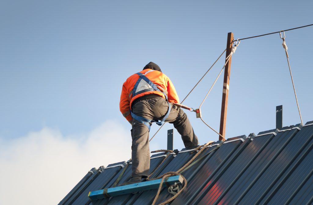 Vue de dos d'un travailleur sur un toit portant un équipement de protection contre les chutes et un harnais complet de Bunzl-Sécurité.