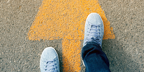 A close crop of two feet wearing white sneakers walking on a big yellow arrow on the road.
