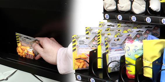 Main tendue pour saisir des bouche-oreilles d'un distributeur automatique d'EPI de Bunzl-Sécurité.