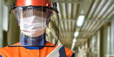 Female wearing an orange hard hat, face mask and shield and industrial grade safety jacket standing in a hallway.