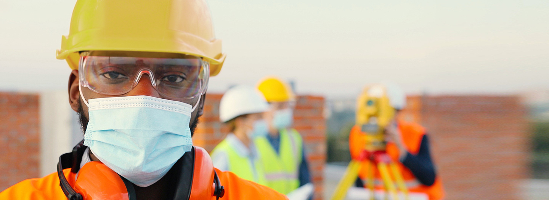Jeune ouvrier noir du secteur de la construction portant un casque de protection jaune, une veste de sécurité orange, une protection pour les yeux et les oreilles, et un masque de Bunzl-Sécurité.