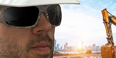 Close up of a man's face wearing protective eye glasses from Bunzl Safety, while at a construction site.