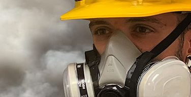 A close crop of a man wearing a yellow hard hat and an industrial grade respirator from Bunzl Safety.