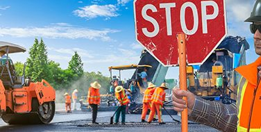 A close crop of a man holding a stop sign at a construction site where everyone is wearing flourescent orange safety vests from Bunzl Safety.