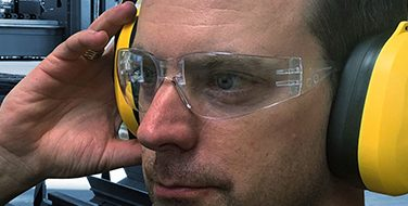 Close crop image of a man wearing yellow hearing protection earmuffs and safety goggles from Bunzl Safety.