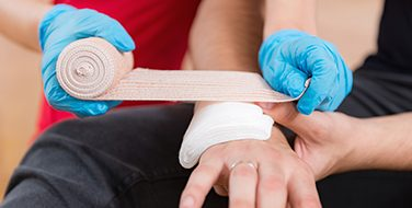 Cropped image of blue vinyl gloved hands dressing a hand injury with first aid supplies from Bunzl Safety.